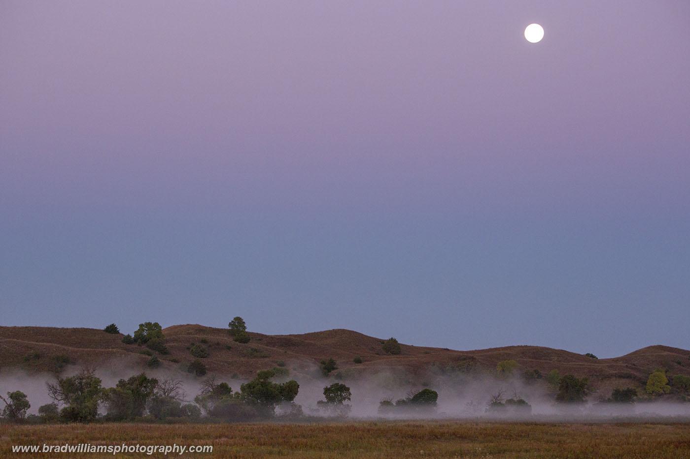 The full moon is setting in the sandhillsas fog is rising off the Middle LoupRiver near Halsey, Nebraska, just outside...
